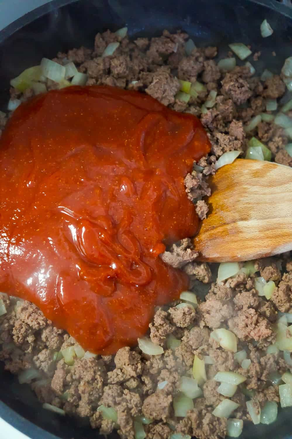 sloppy joe sauce added to cooked ground beef in a frying pan