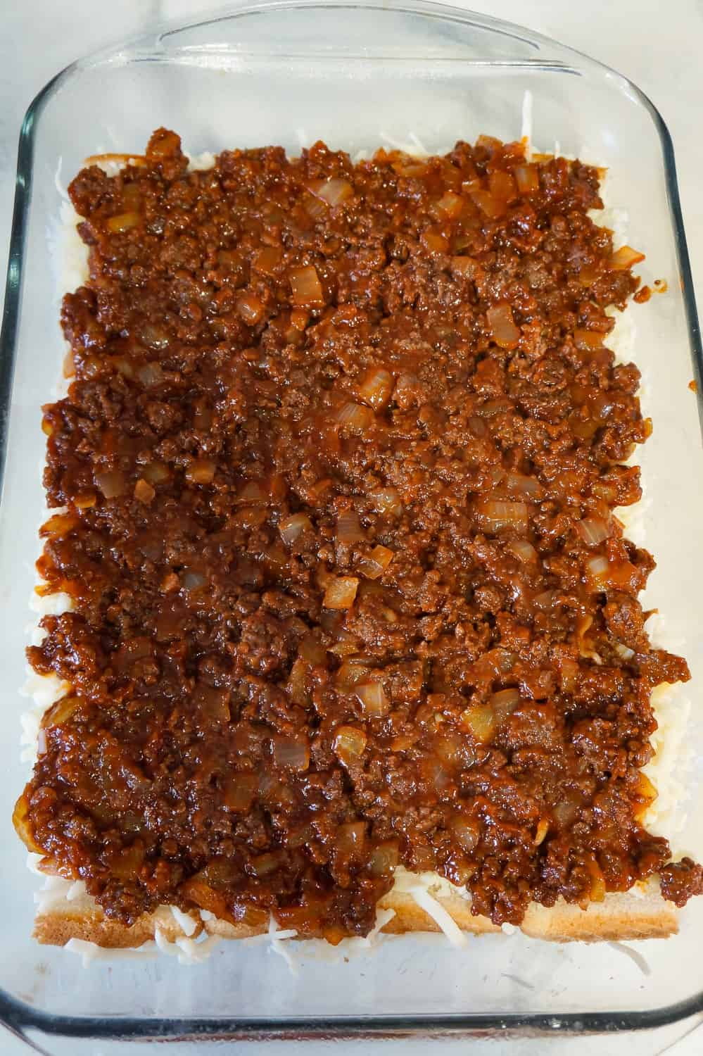 sloppy joe mixture spread over bread in a baking dish