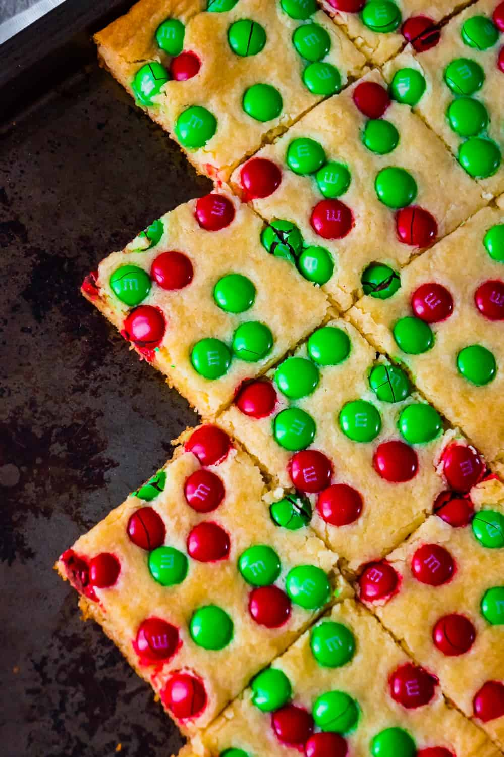 Christmas Cookie Bars are an easy holiday dessert recipe. These vanilla pudding sugar cookie bars are loaded with red and green M&M's.