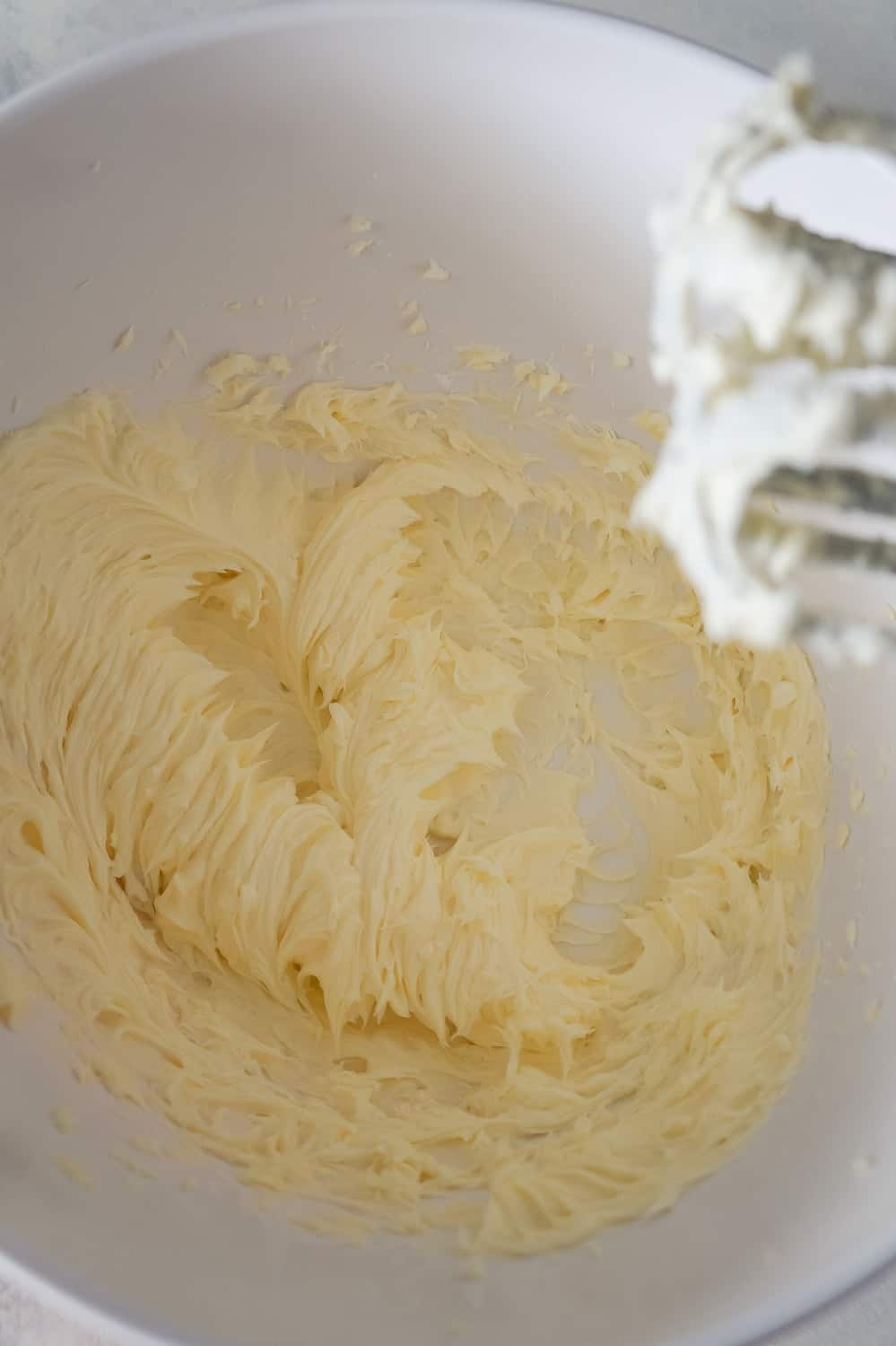 whipped butter and icing sugar in a mixing bowl