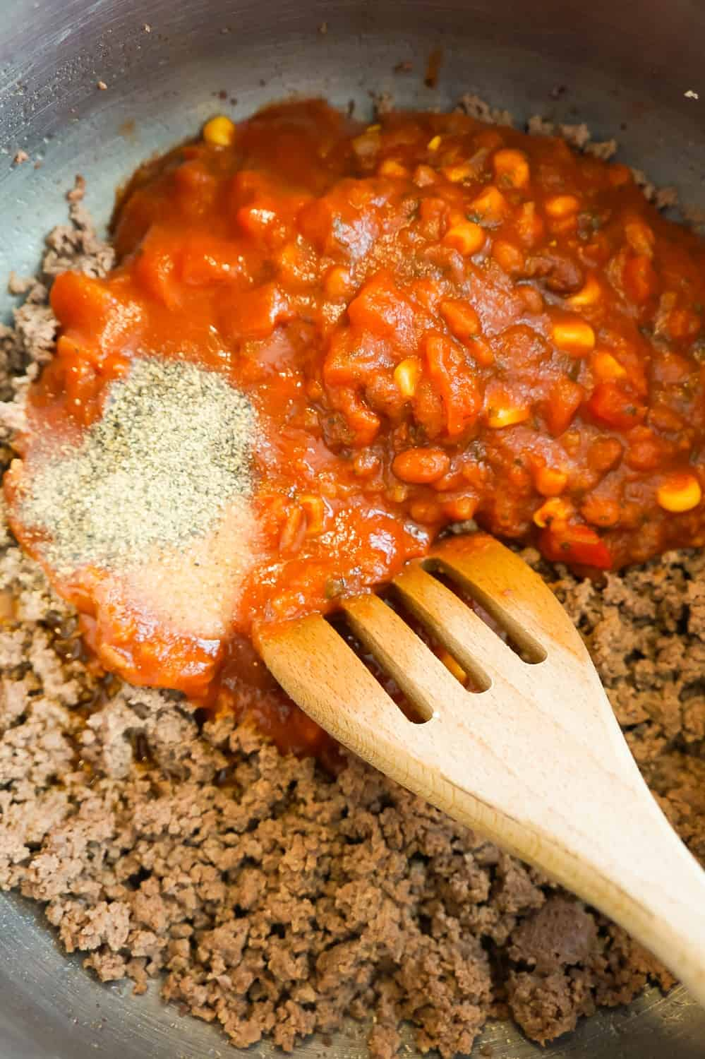 salsa and taco sauce poured over cooked ground beef in a pot