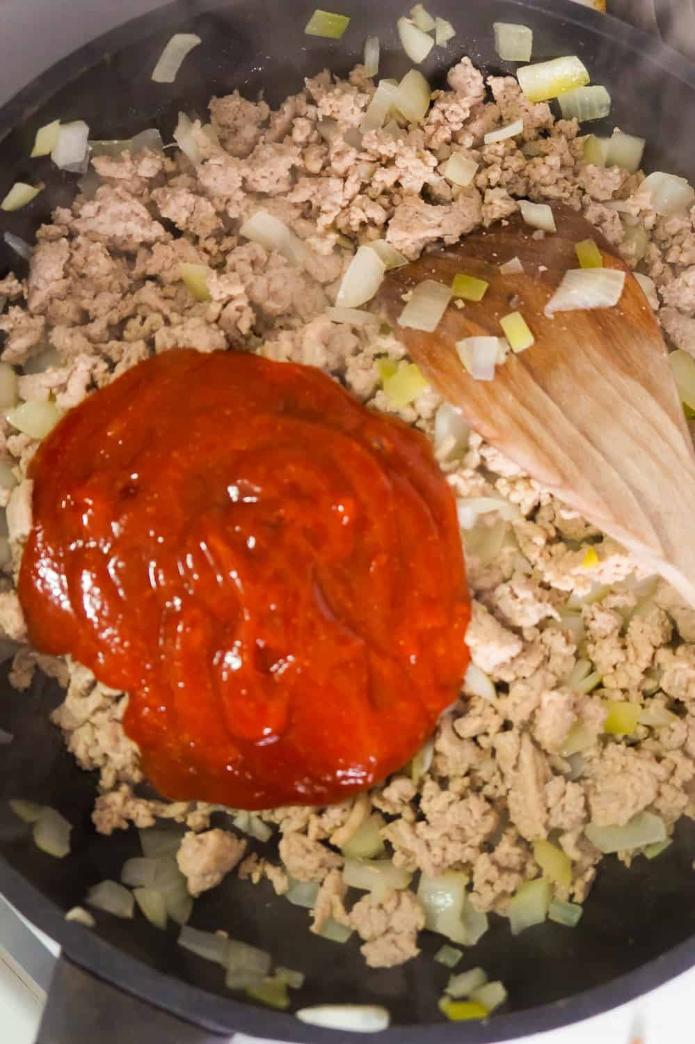 sloppy joe sauce on top of cooked ground turkey in a frying pan