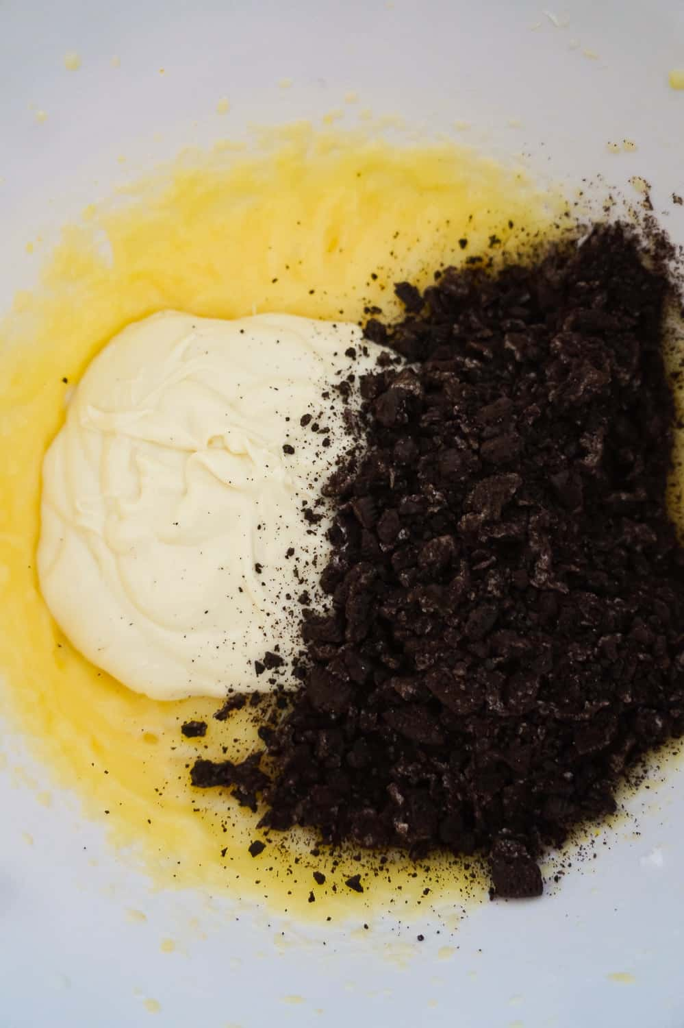 melted white chocolate and crushed Oreo cookies added to vanilla pudding mixture in mixing bowl