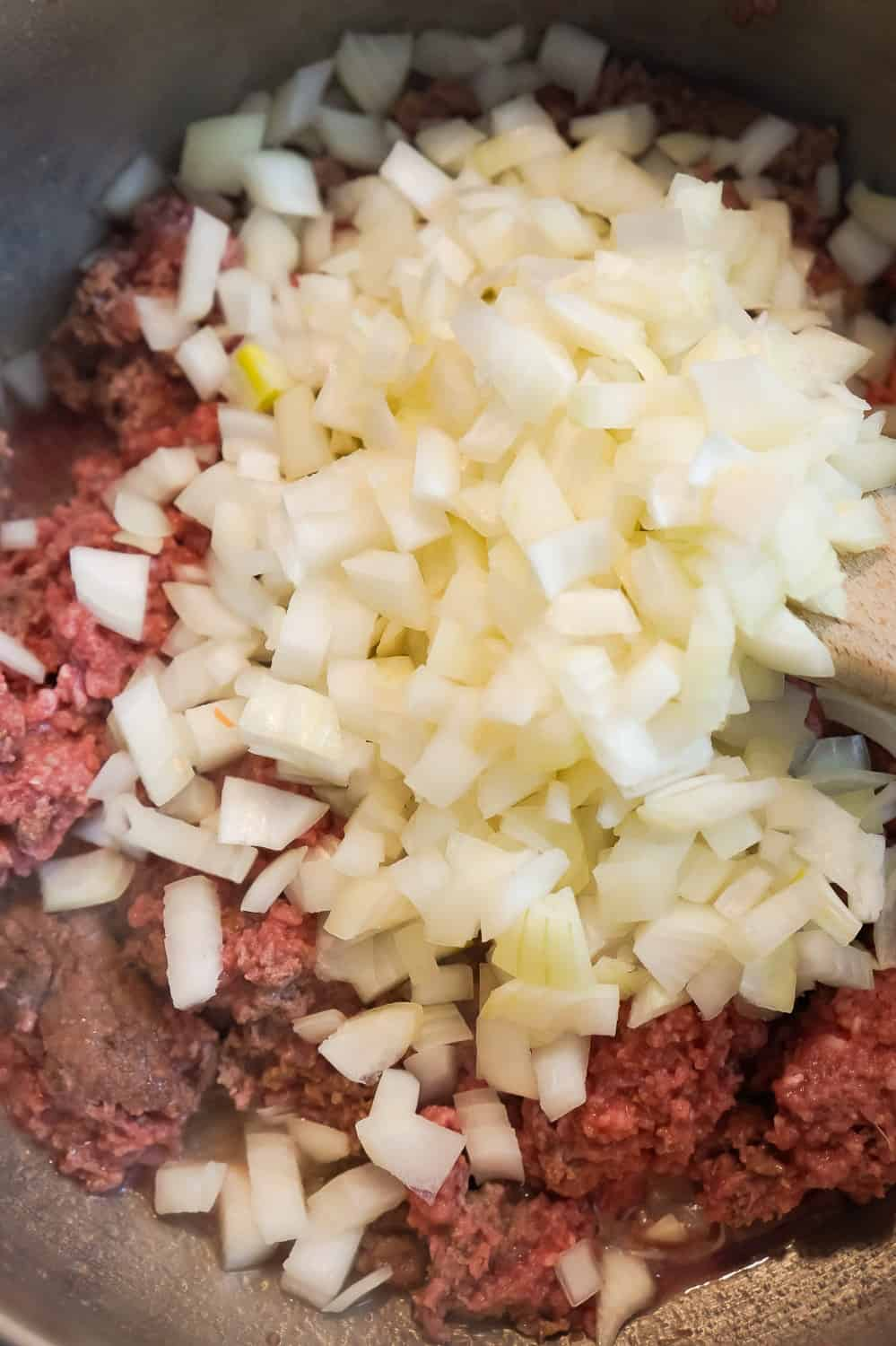 diced onions and ground beef cooking in a pan