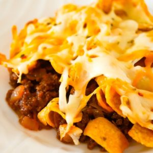 Sloppy Joe Frito Pie is a delicious casserole recipe with ground beef and onions tossed in homemade sloppy joe sauce and topped with Fritos corn chips and shredded cheese.