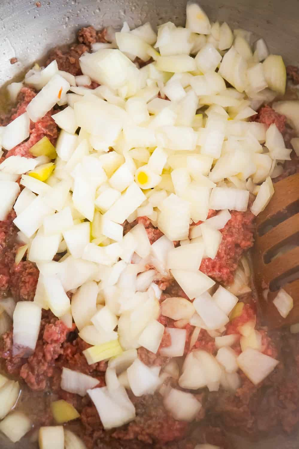 diced onions and ground beef in a pan