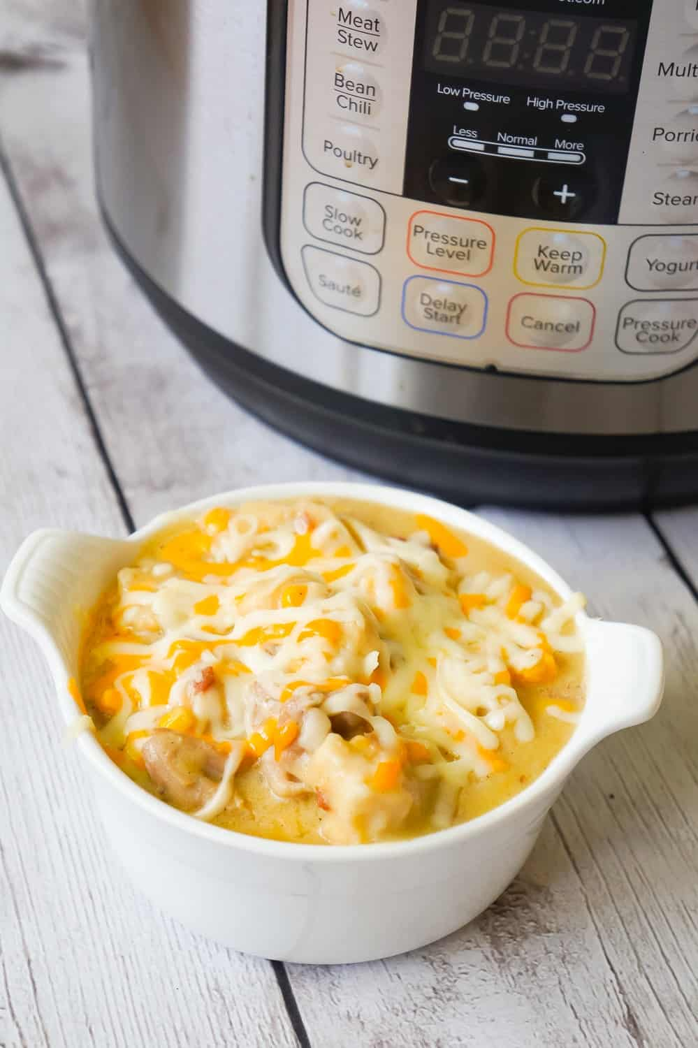 Instant Pot Chicken and Dumplings is an easy dinner recipe using boneless, skinless chicken thighs. This chicken and dumpling recipe uses Pillsbury refrigerated biscuit dough and is loaded with cheese and bacon.