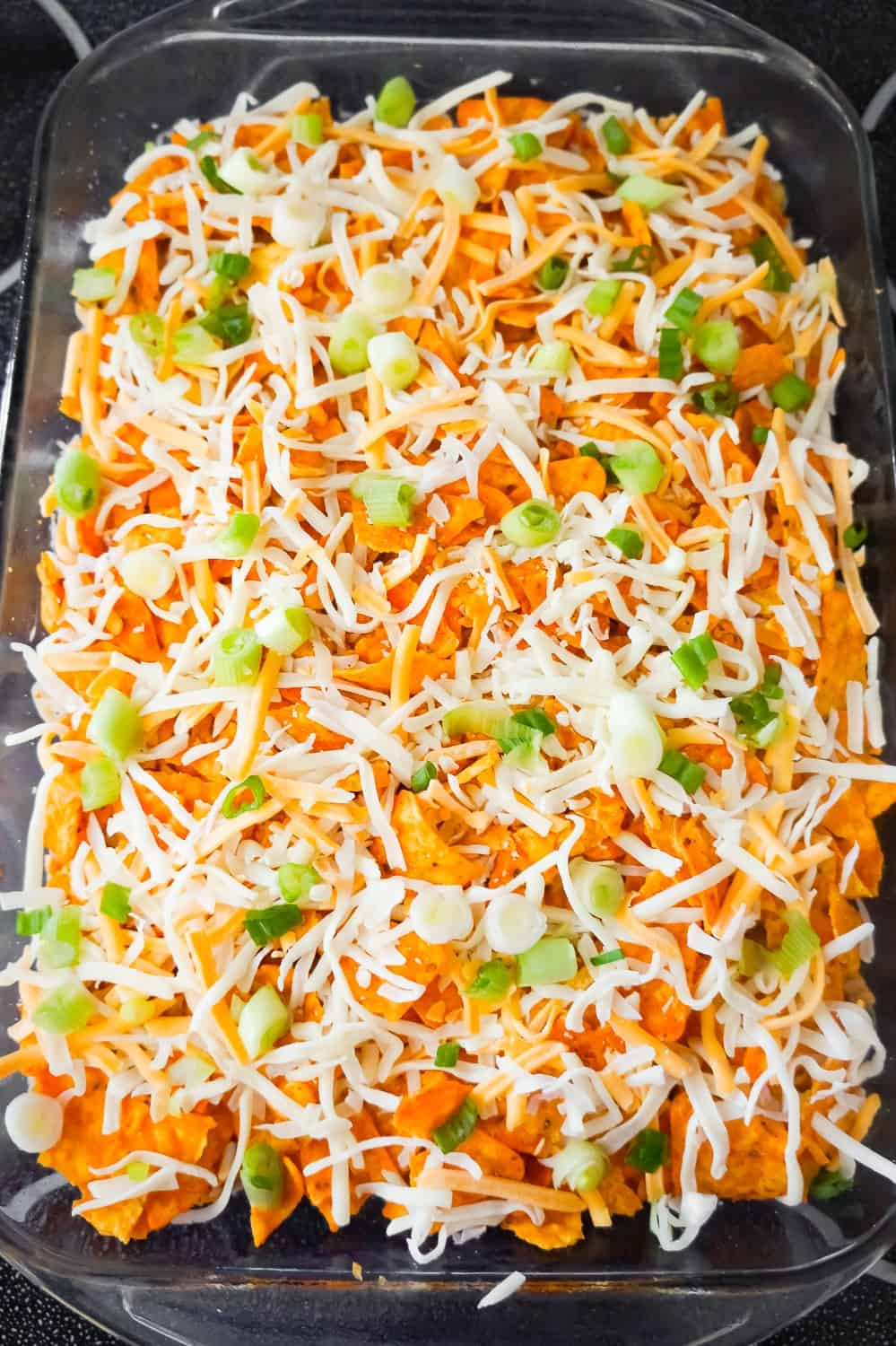 shredded cheese and chopped green onions on top of crumbled Doritos