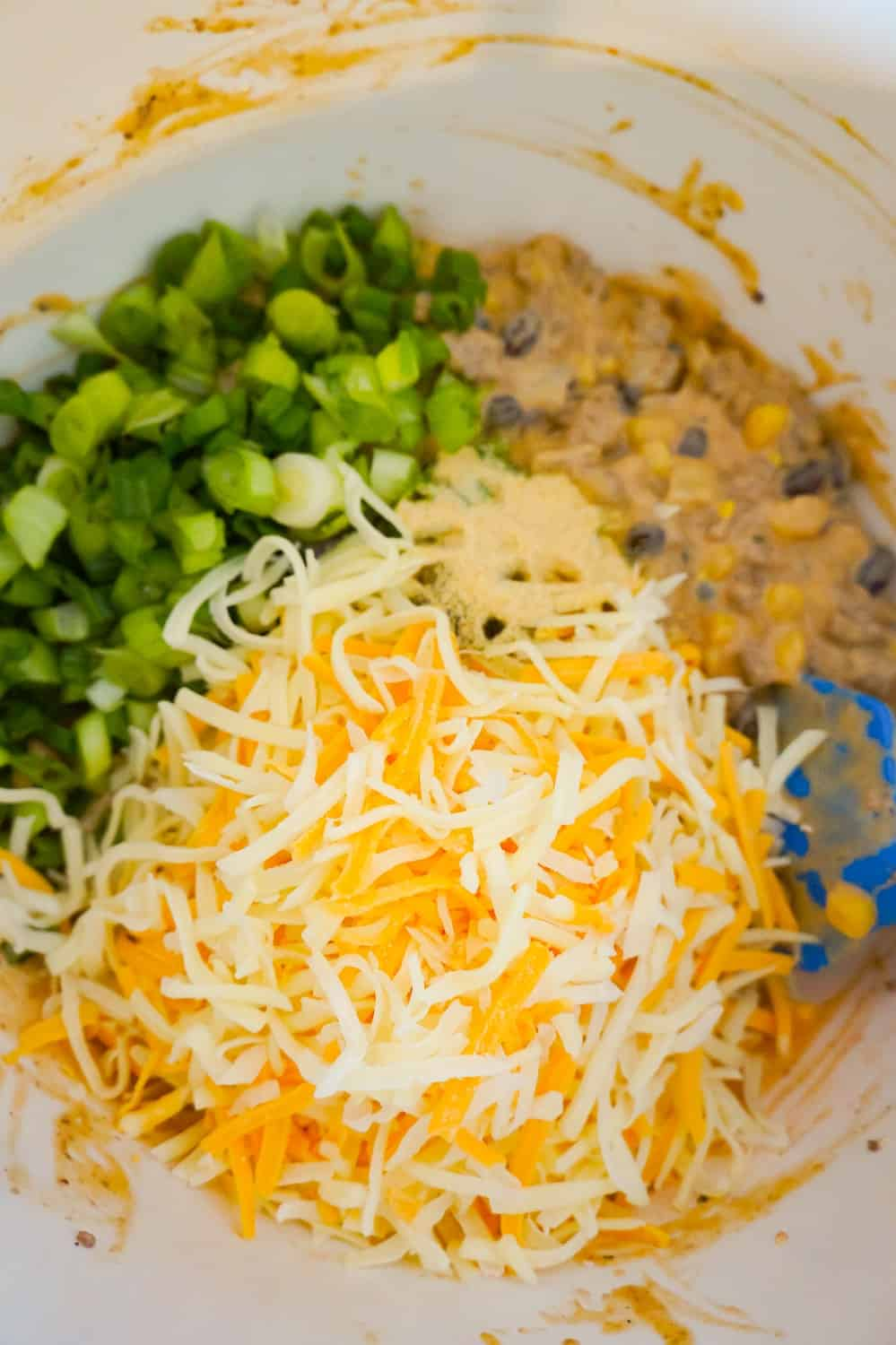 shredded cheese, chopped green onions and ground beef mixture in a mixing bowl