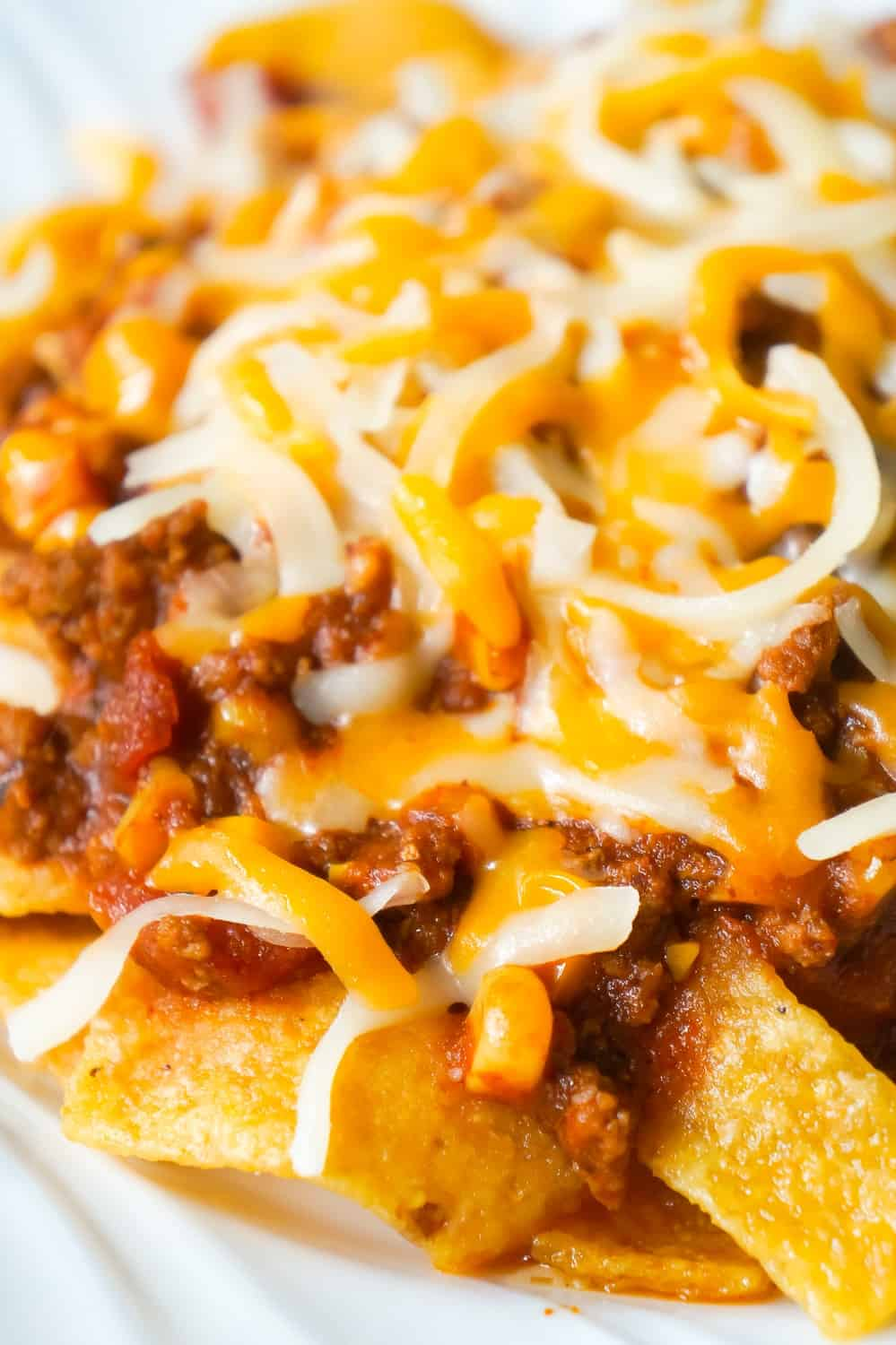 Instant Pot Frito Pie is an easy ground beef dinner recipe the whole family will love. A delicious ground beef and corn chili mixture is cooked in the Instant Pot and then poured over Frito's corn chips and topped with shredded cheese.