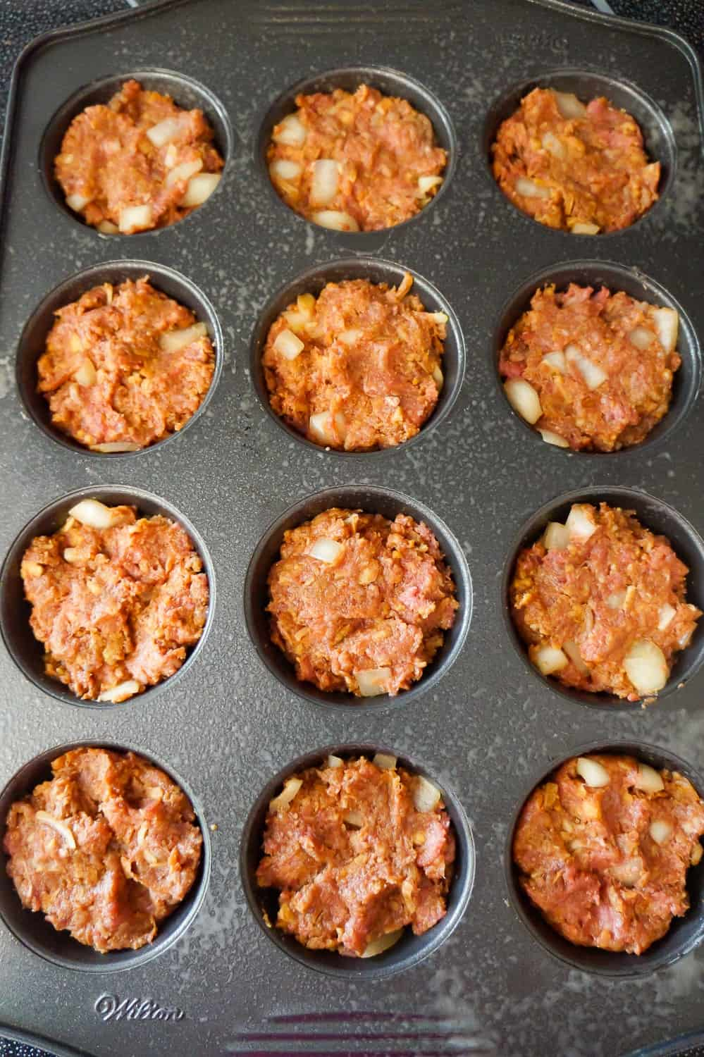 meatloaf mixture pressed into muffin tins
