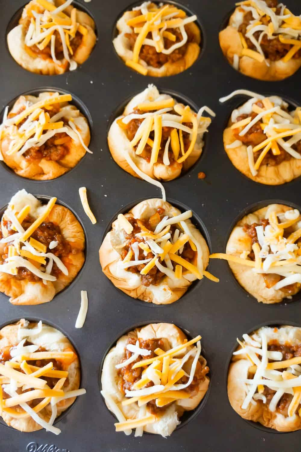 sloppy joe hamburger bun cups with shredded cheese on top before baking