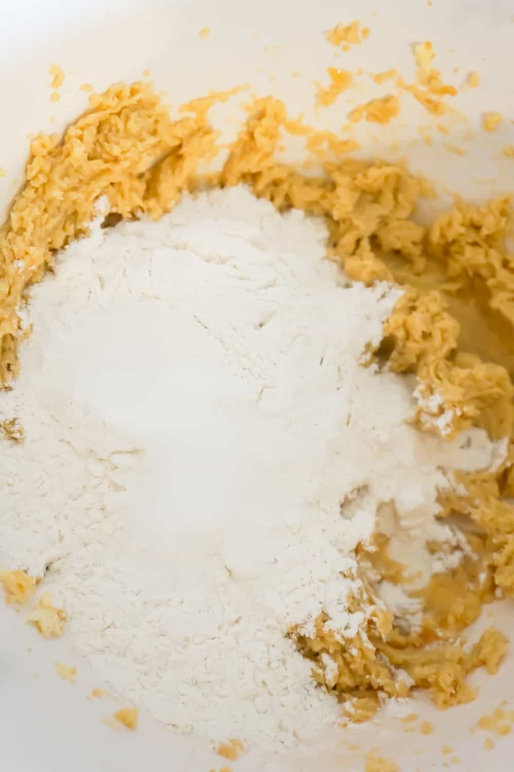 flour on top of butter and sugar mixture in a mixing bowl