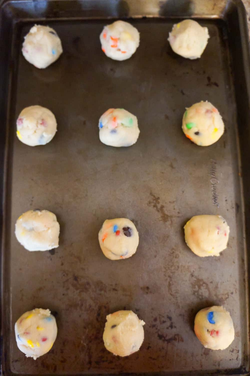 M&M cookie dough balls on a baking sheet