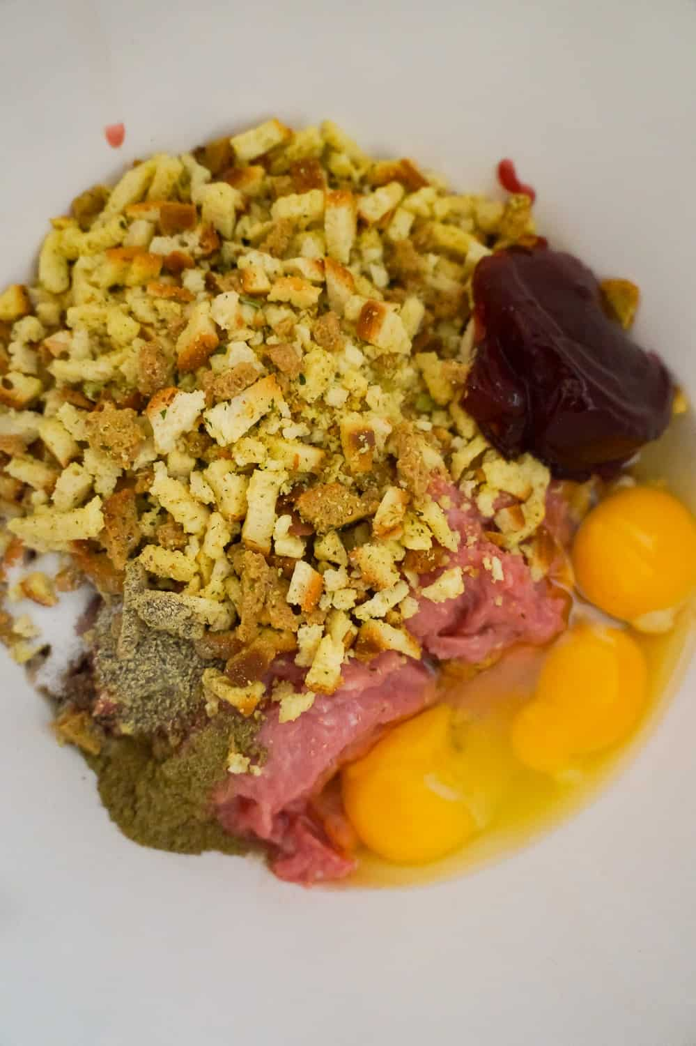 stove top stuffing mix, cranberry sauce and eggs on top of ground turkey in a mixing bowl