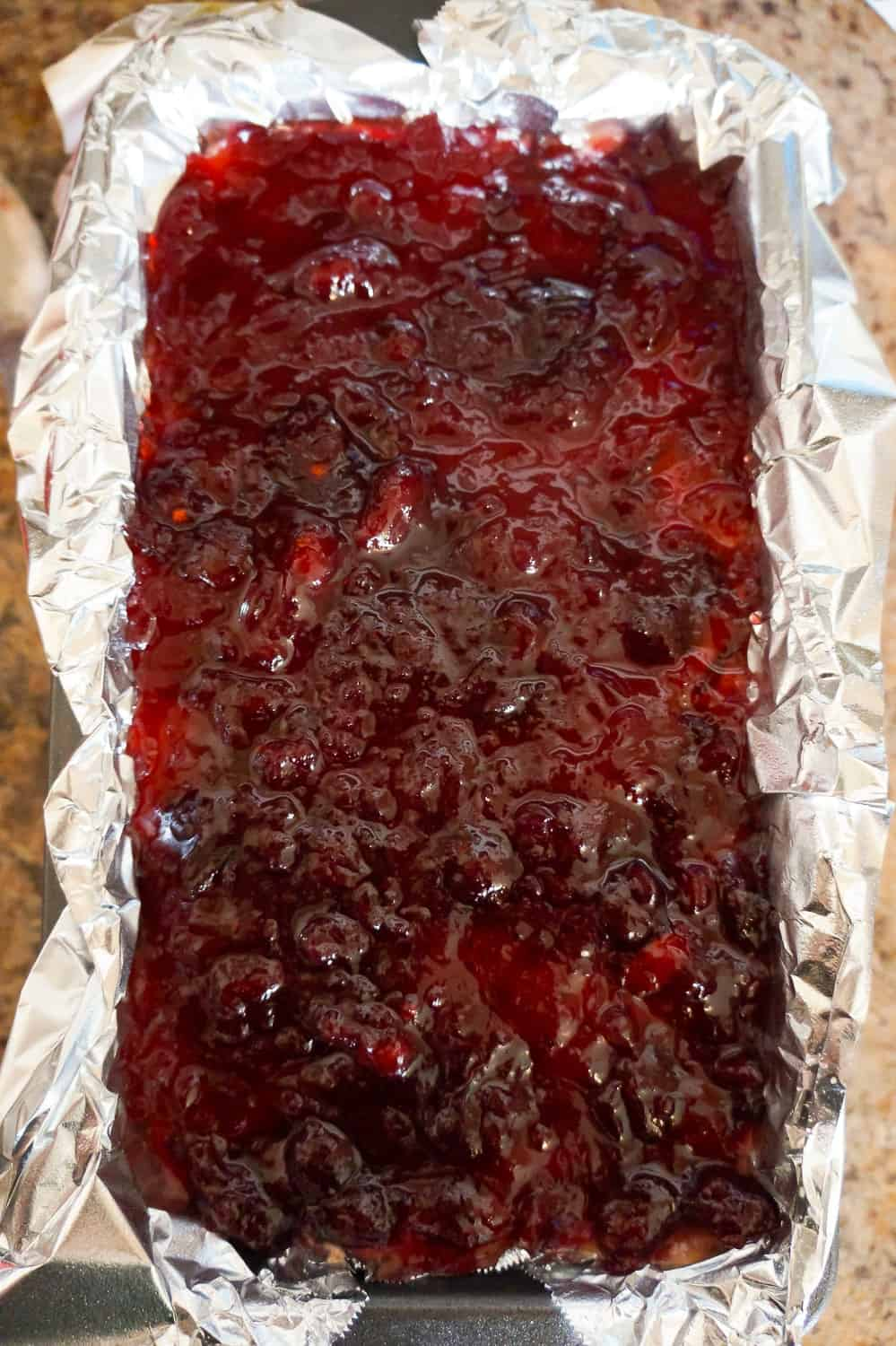 cranberry sauce on top of turkey meatloaf in a loaf pan