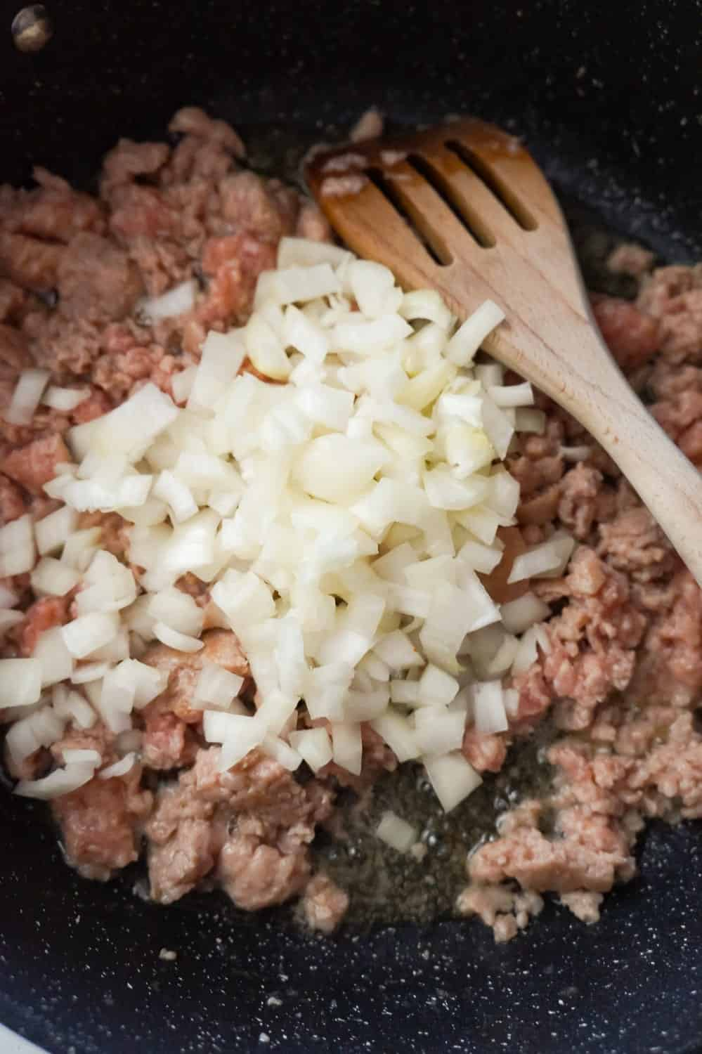 diced onions on top of raw ground sausage meat in a frying pan