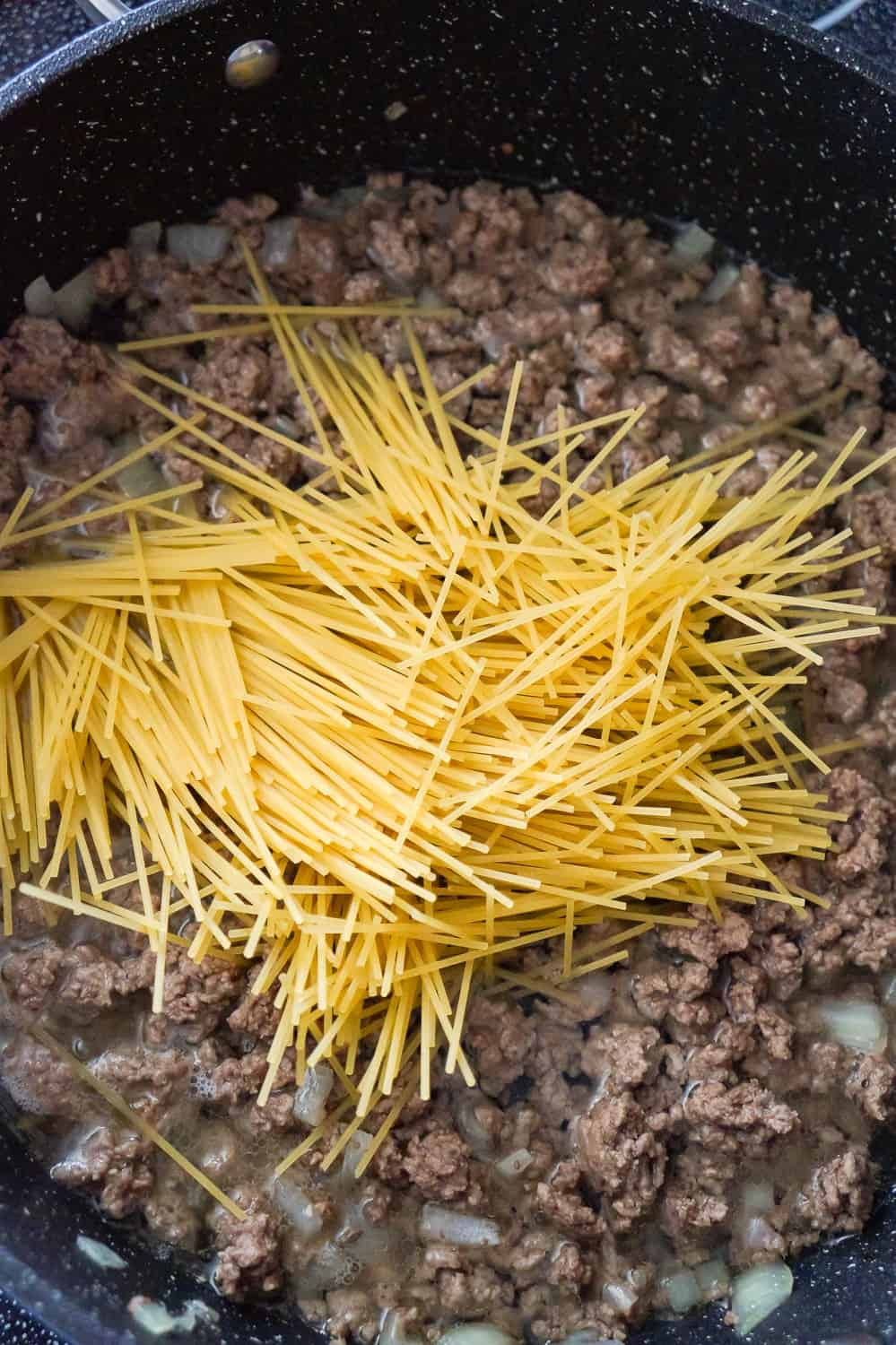 uncooked spaghetti noodles on top of ground beef and water in a saute pan