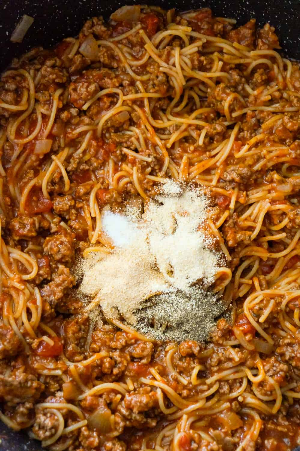 spices on top of spaghetti bolognese in a pan.