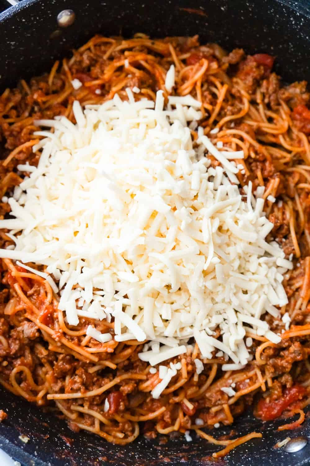shredded mozzarella on top of spaghetti bolognese in a pan