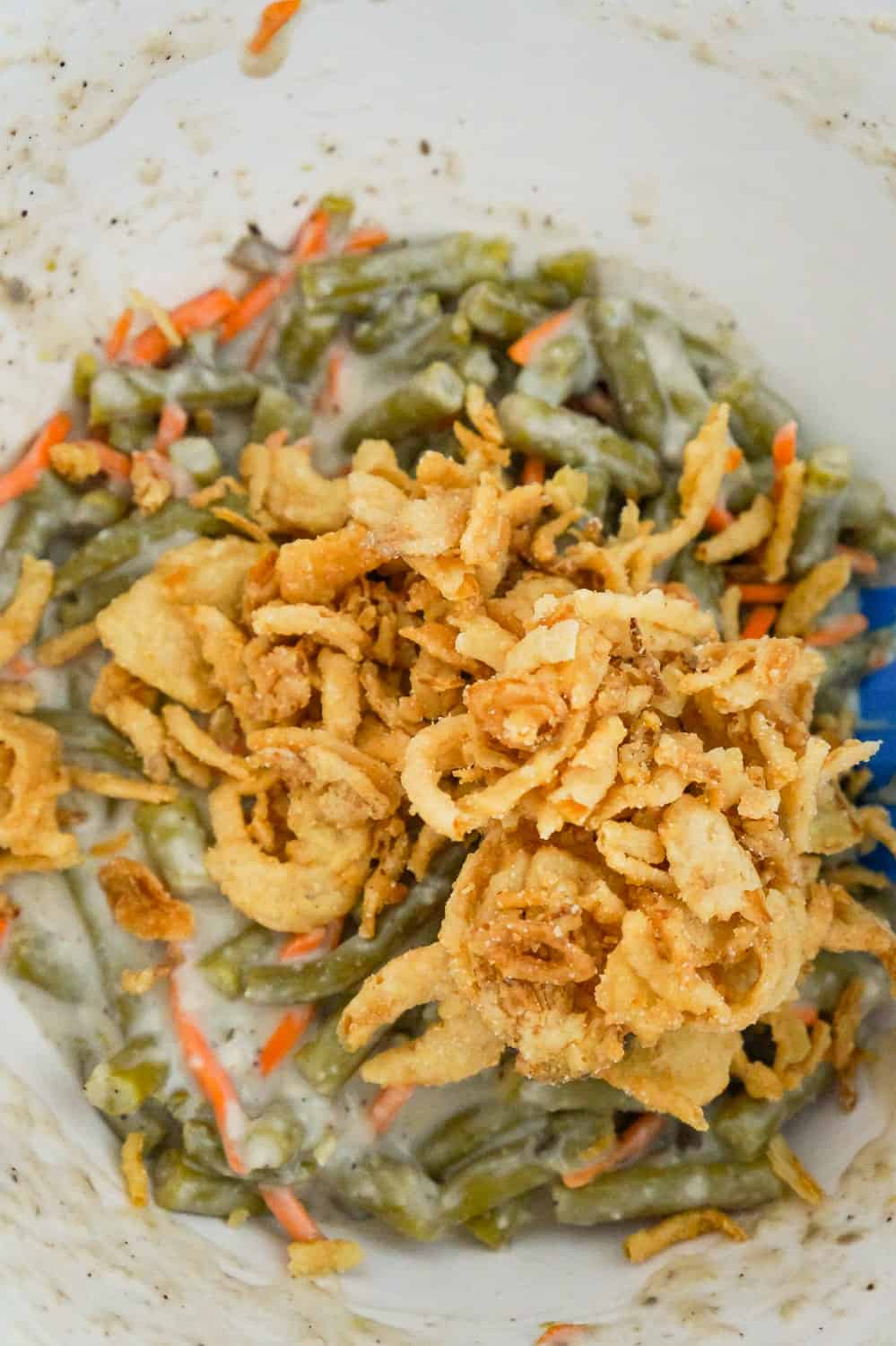 French's fried onions on top of green bean and carrot mixture in a mixing bowl