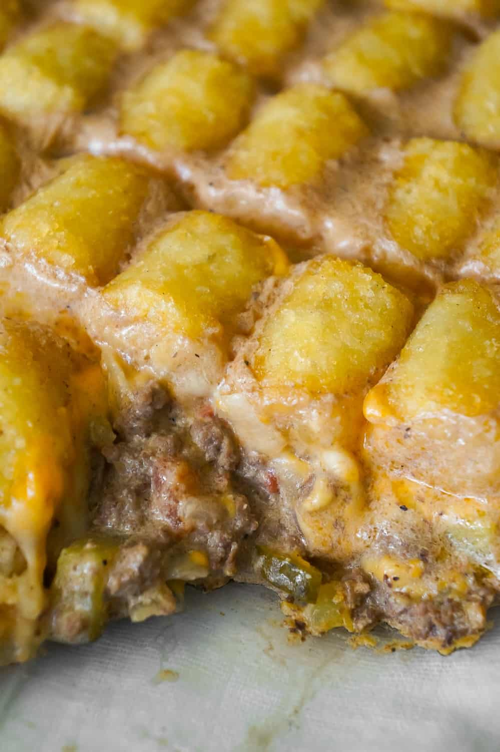 Hamburger Casserole with Tater Tots is an easy ground beef casserole recipe made with cream of mushroom soup, diced dill pickles and diced tomatoes, all topped with cheese and potatoes.