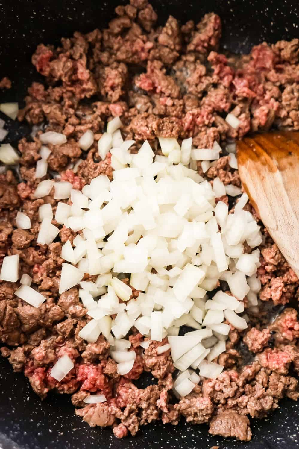 diced onion on top of ground beef in a saute pan