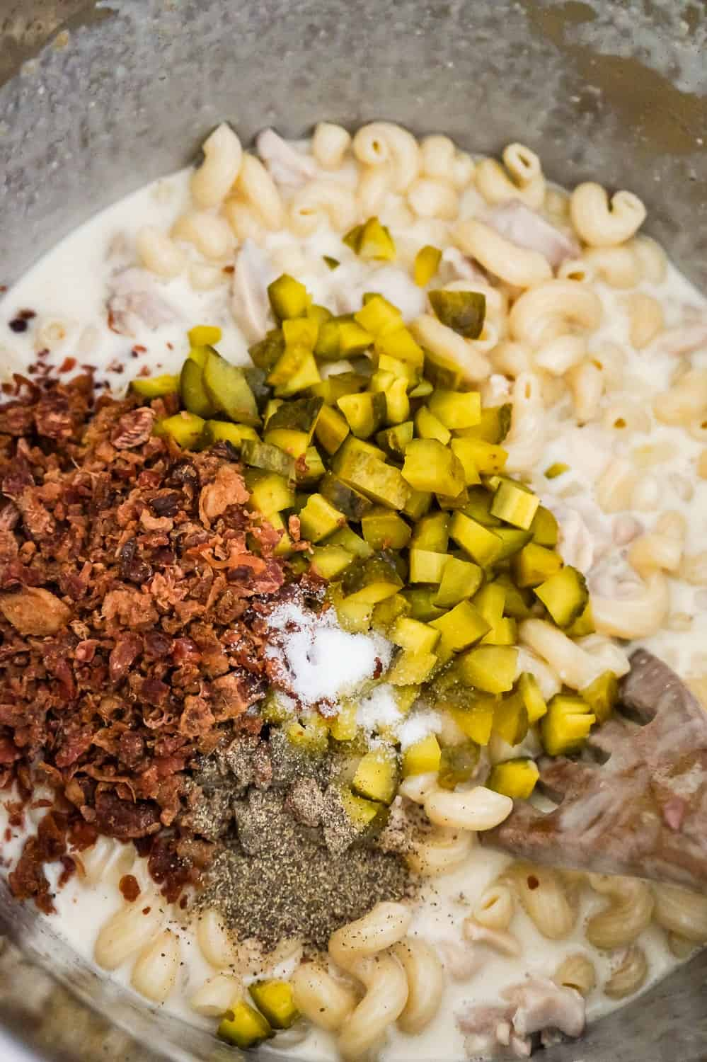 crumbled bacon, spices and diced dill pickles on top of creamy pasta in an Instant Pot