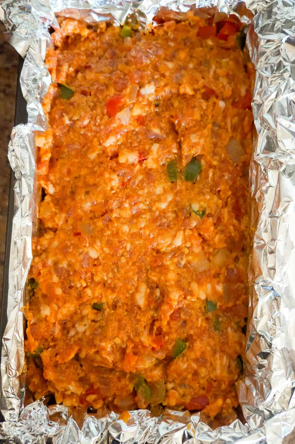 sausage and peppers meatloaf mixture pressed into a loaf pan before baking