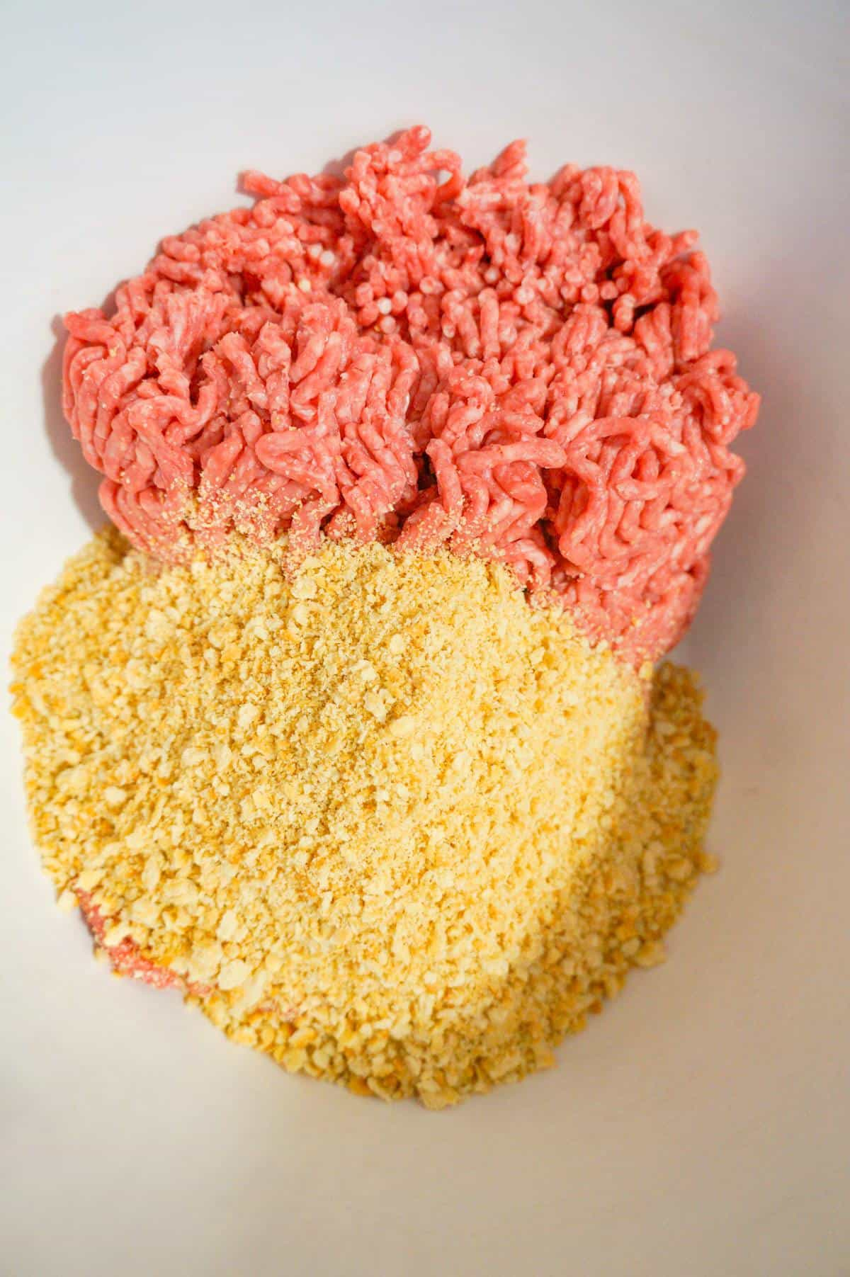 raw ground beef and Ritz cracker crumbs in a mixing bowl