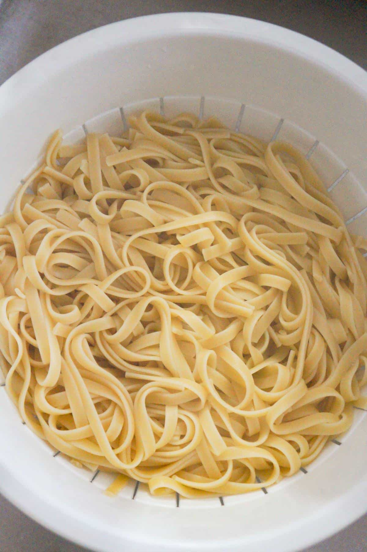 cooked fettuccine in a strainer