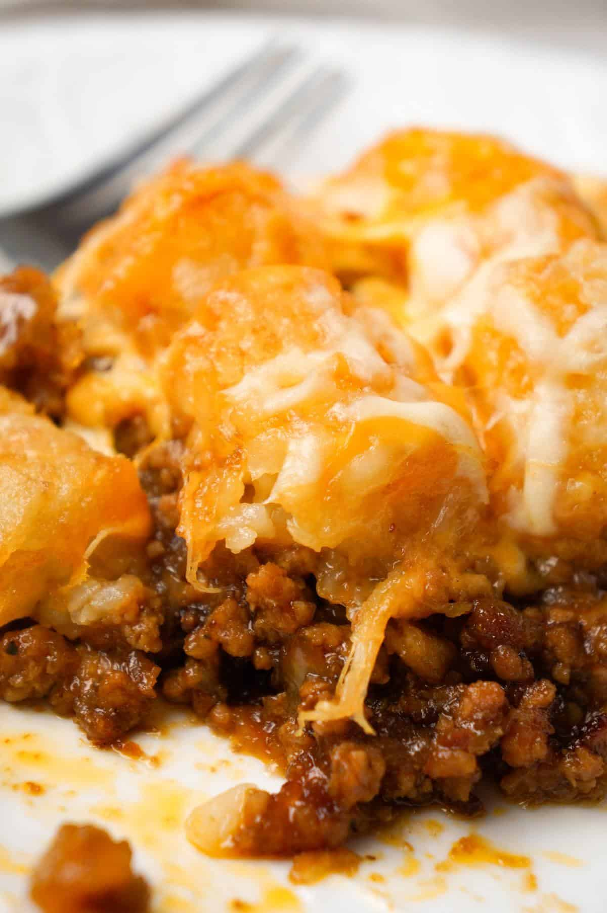 Dr Pepper Pork Tater Tot Casserole is a hearty dish with a base of ground pork cooked in Dr Pepper and BBQ sauce and topped with tater tops and shredded cheese.