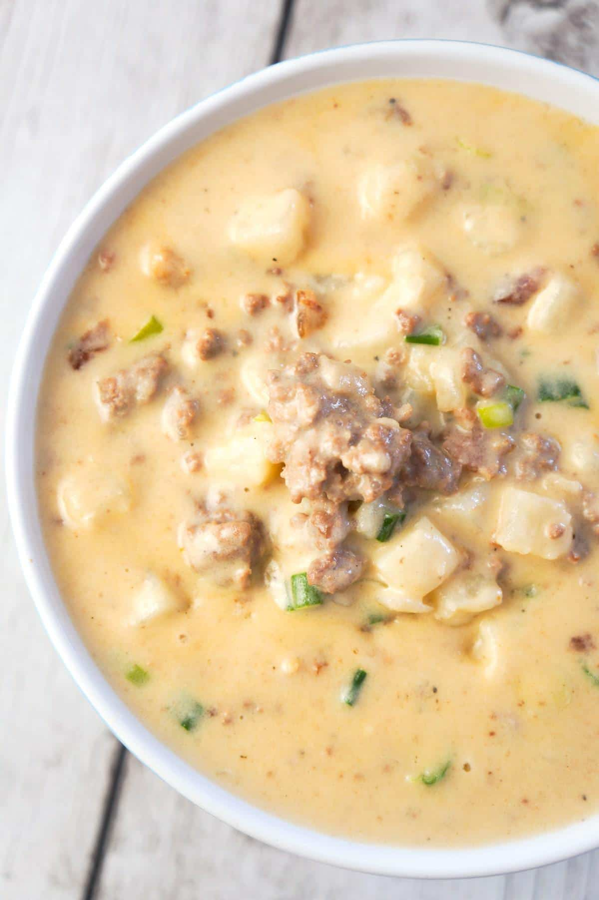 Instant Pot Bacon Cheeseburger Soup with Potatoes is a hearty pressure cooker soup recipe loaded with ground beef, crumbled bacon, diced hash brown potatoes, chopped green onions and cheddar cheese.