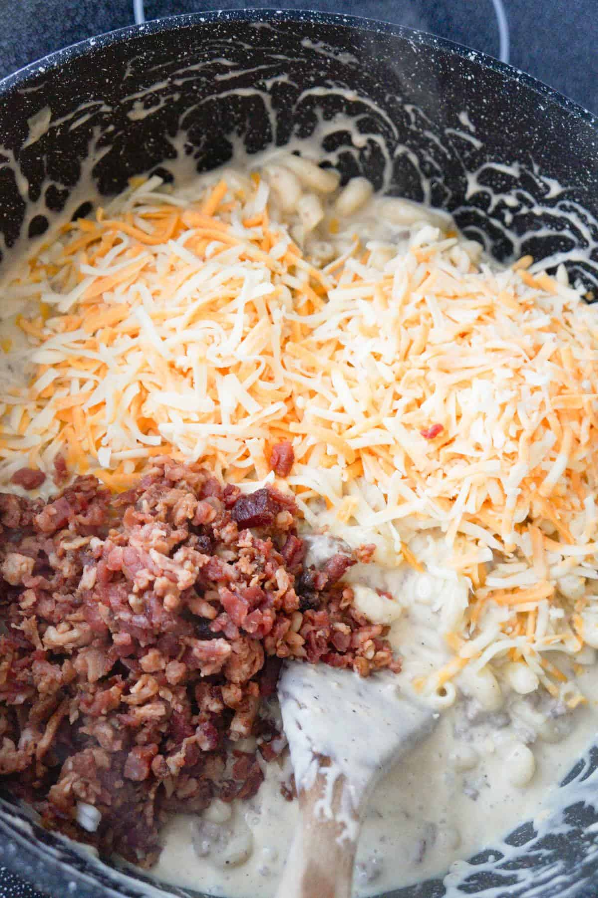 shredded cheese and crumbled bacon on top of creamy pasta in a pot
