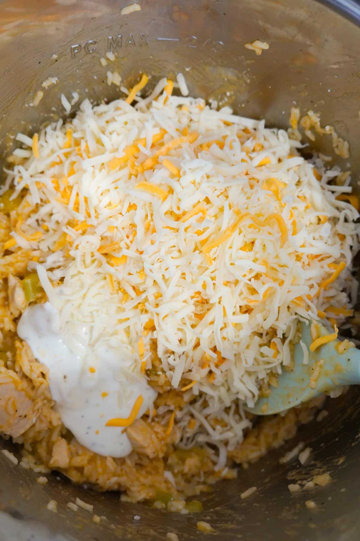 shredded cheese and ranch dressing on top of chicken and rice in an Instant Pot