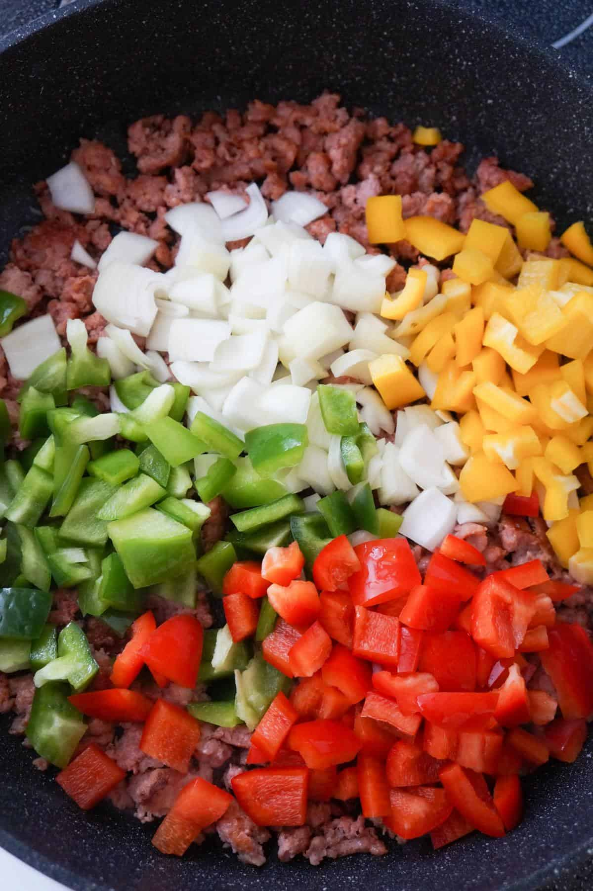 diced onion and diced peppers on top of ground sausage meat in a saute pan