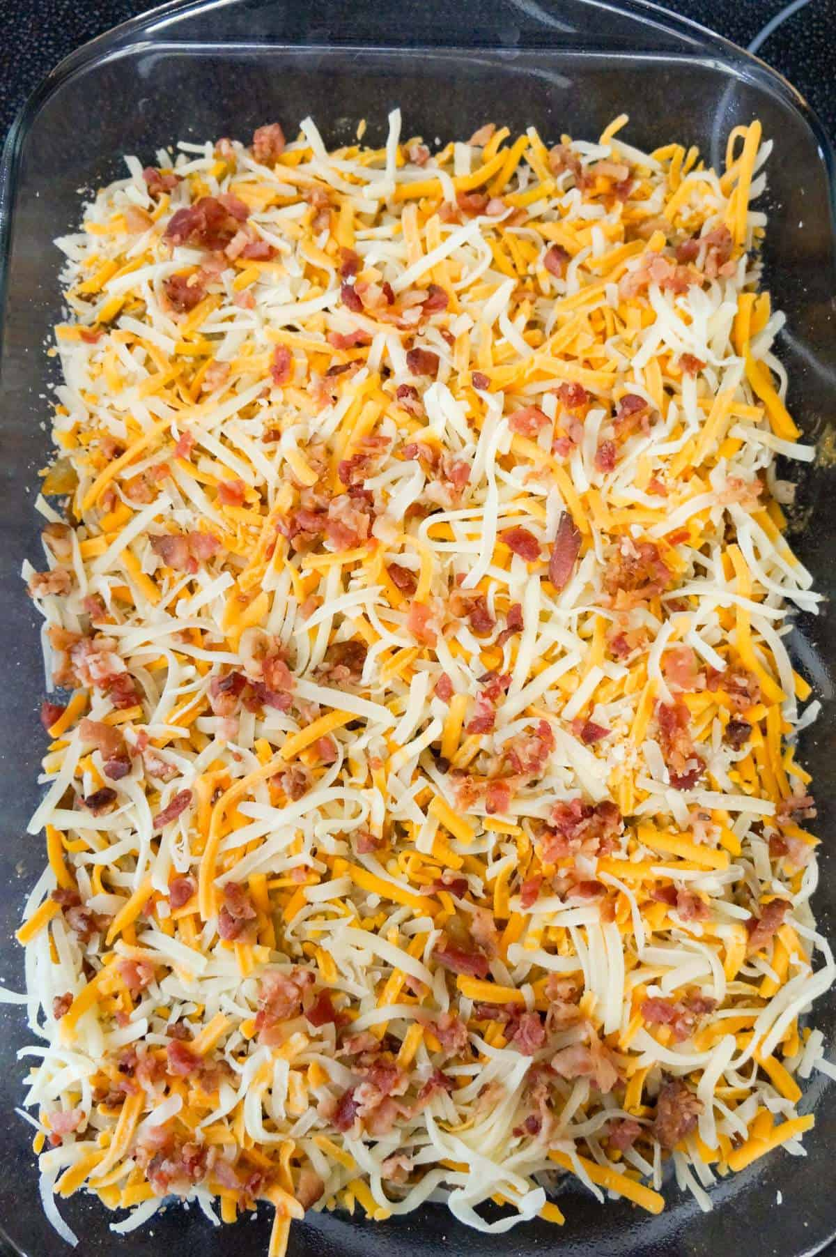 crumbled bacon and shredded cheese on top of cheeseburger casserole before baking