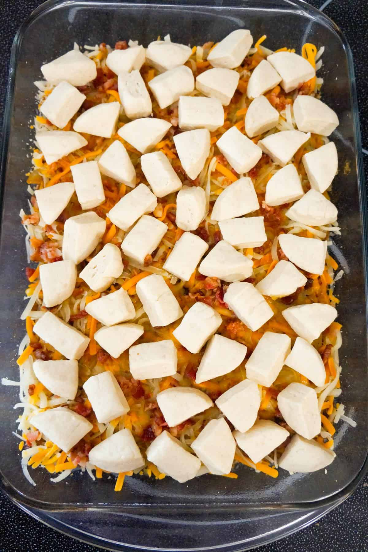Pillsbury biscuit dough pieces on top of bacon cheeseburger casserole before baking