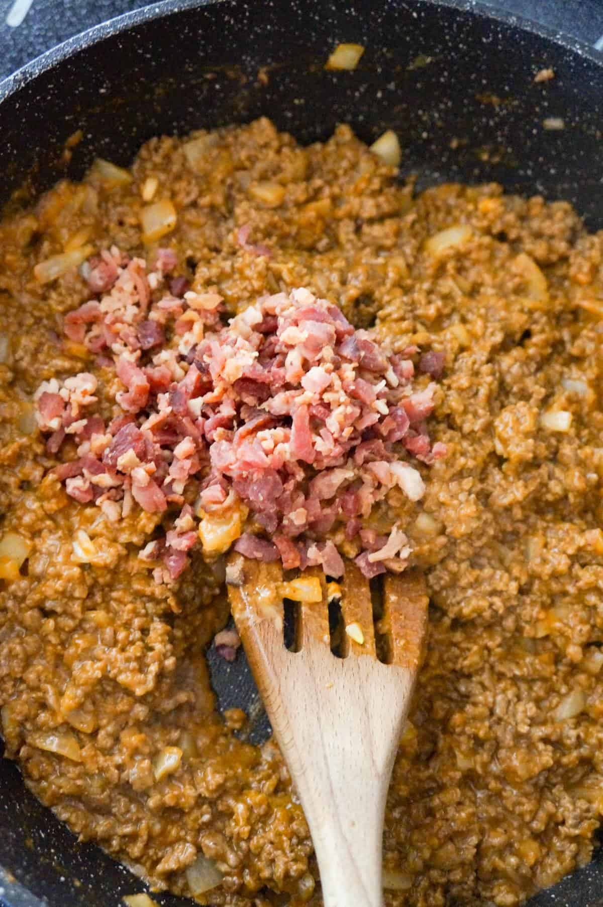 crumbled bacon on top of ground beef mixture in a saute pan