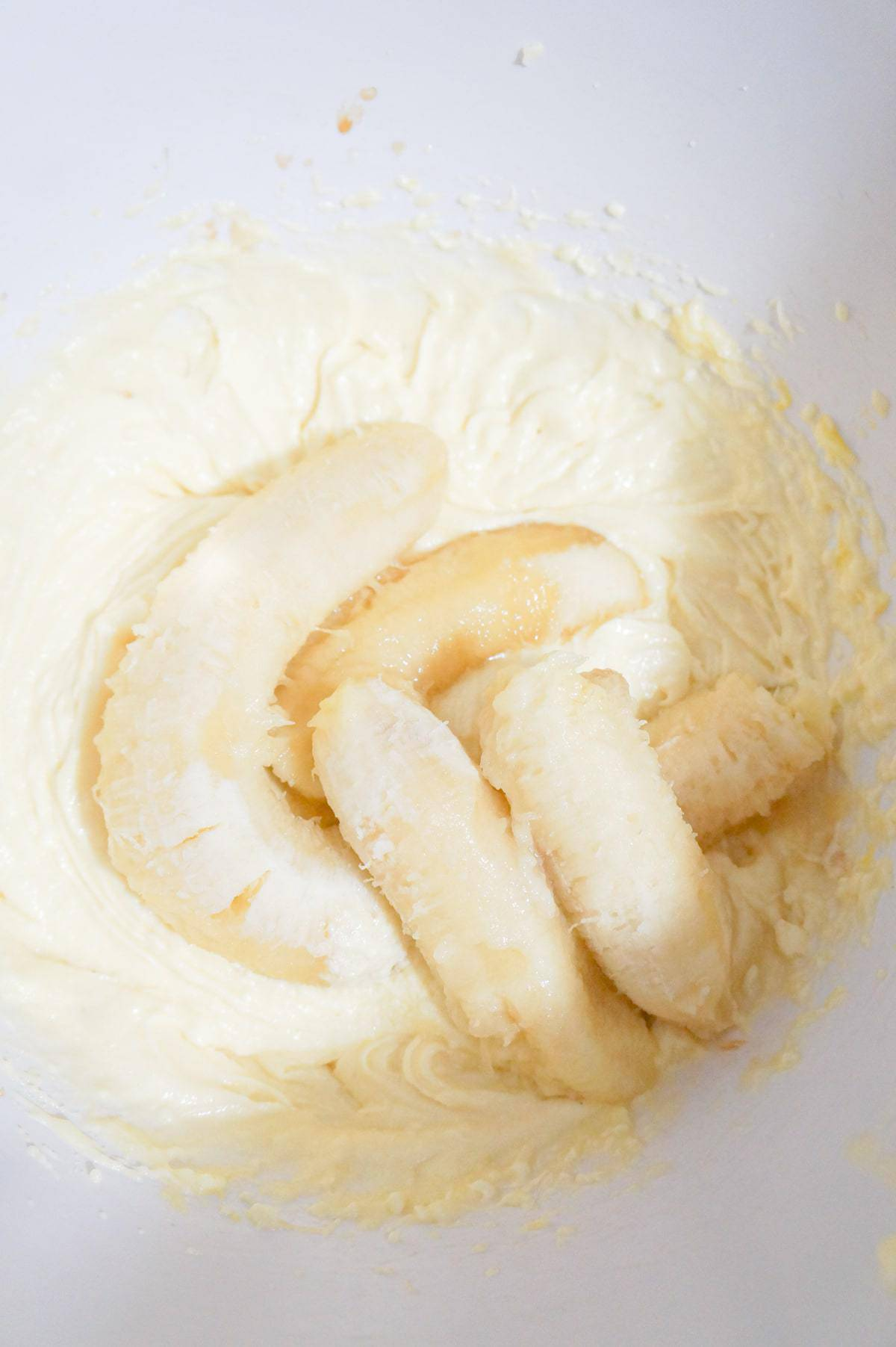 ripe bananas on top of cream butter and sugar mixture in a mixing bowl