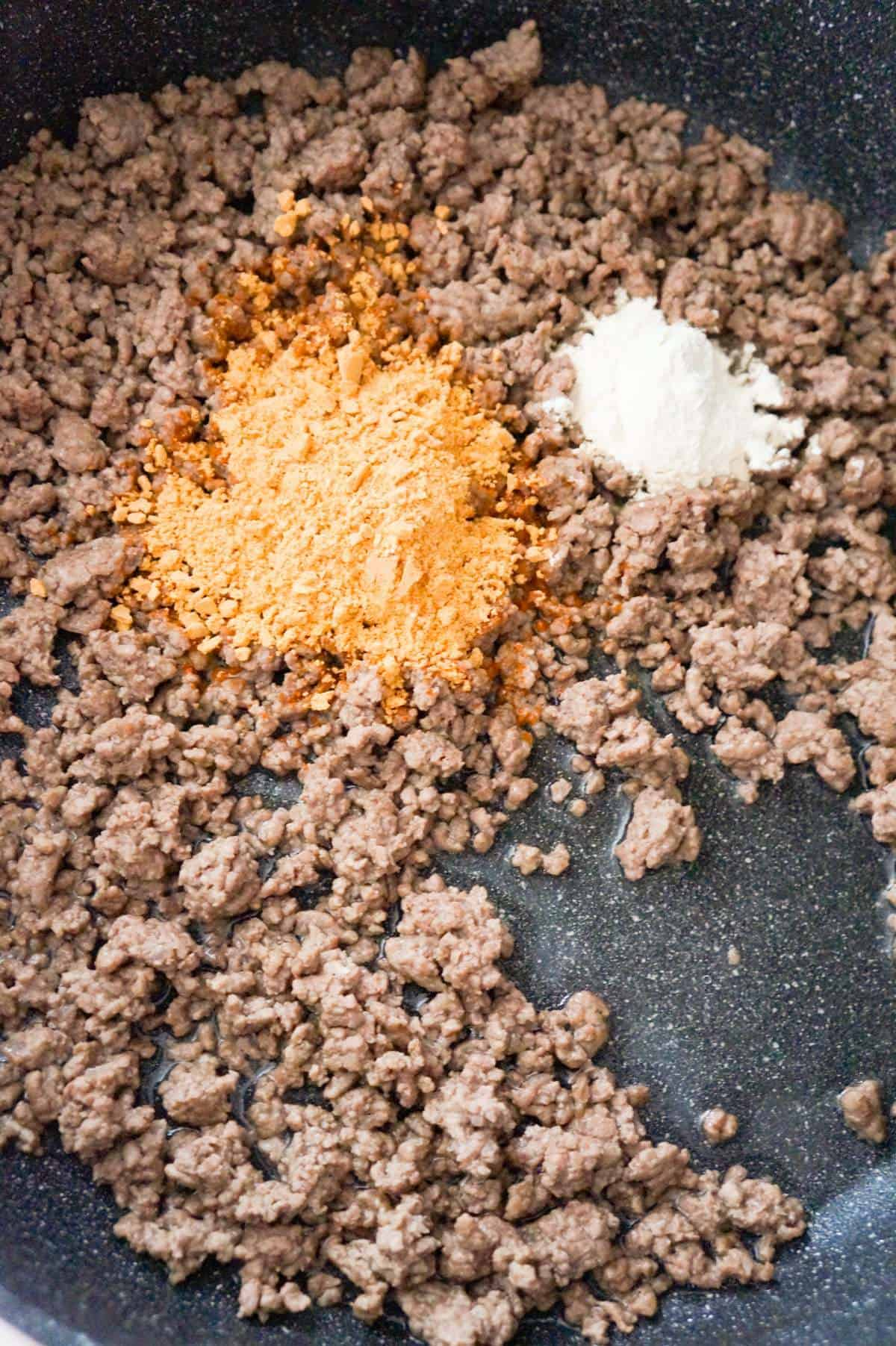 taco seasoning and onion powder on top of cooked ground beef in a pan