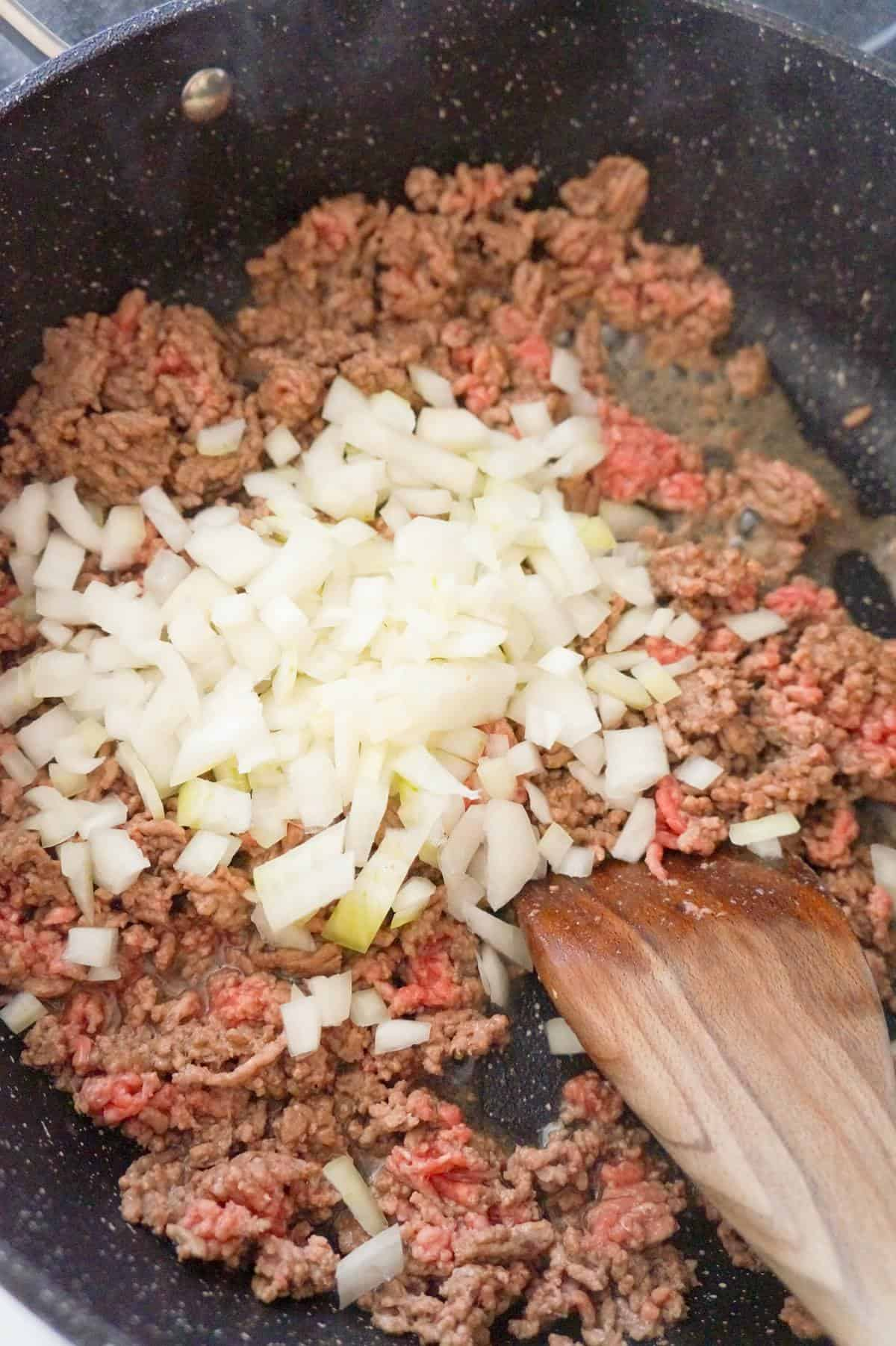 diced onions on top of ground beef in a saute pan
