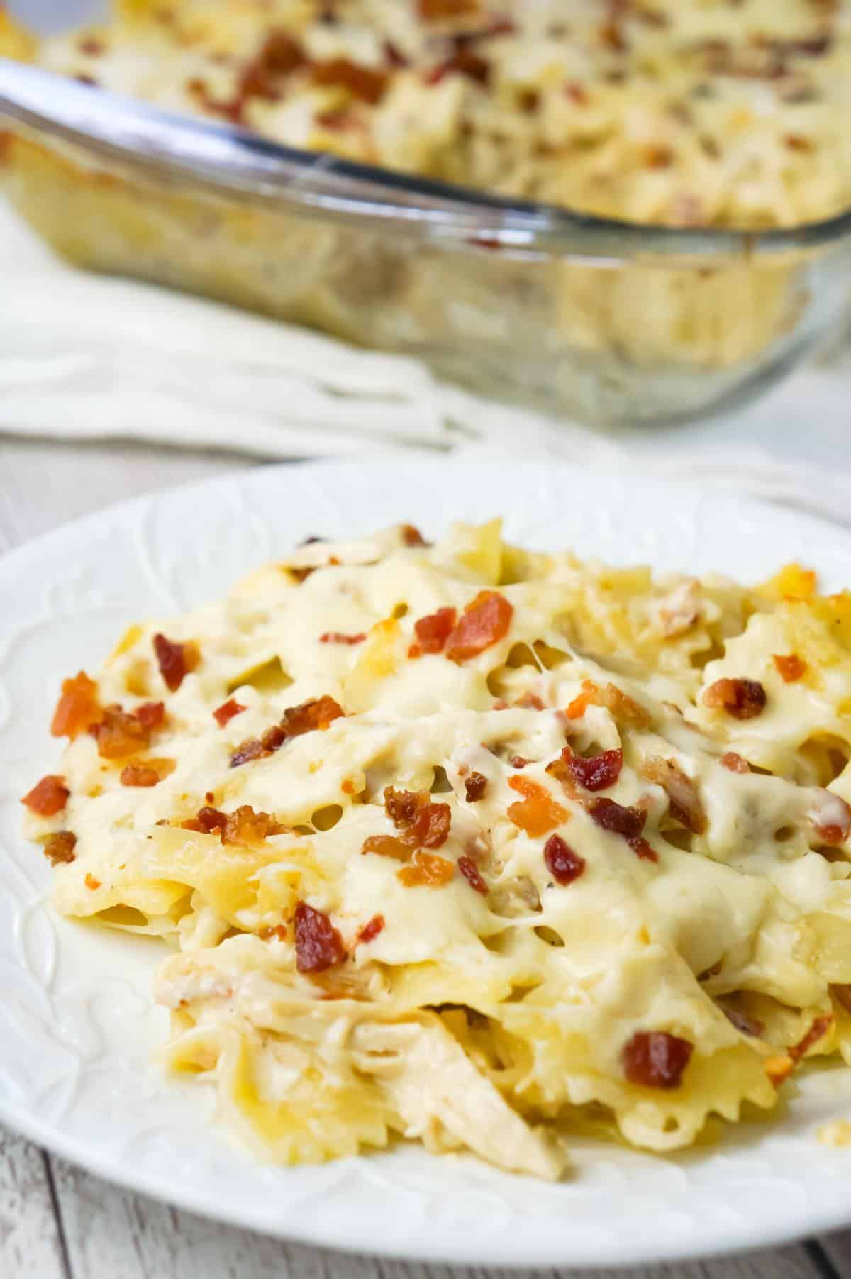 Baked Chicken Alfredo Pasta with Bacon is a delicious dinner recipe loaded with bow tie pasta, shredded chicken and crumbled bacon all in a creamy garlic Parmesan sauce and baked with mozzarella on top.