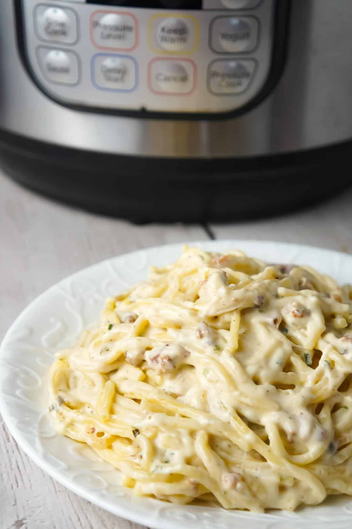 Instant Pot Bacon Cream Cheese Spaghetti is an easy pasta recipe made with heavy cream, chive and onion cream cheese, cream of bacon soup, shredded cheese and crumbled bacon.