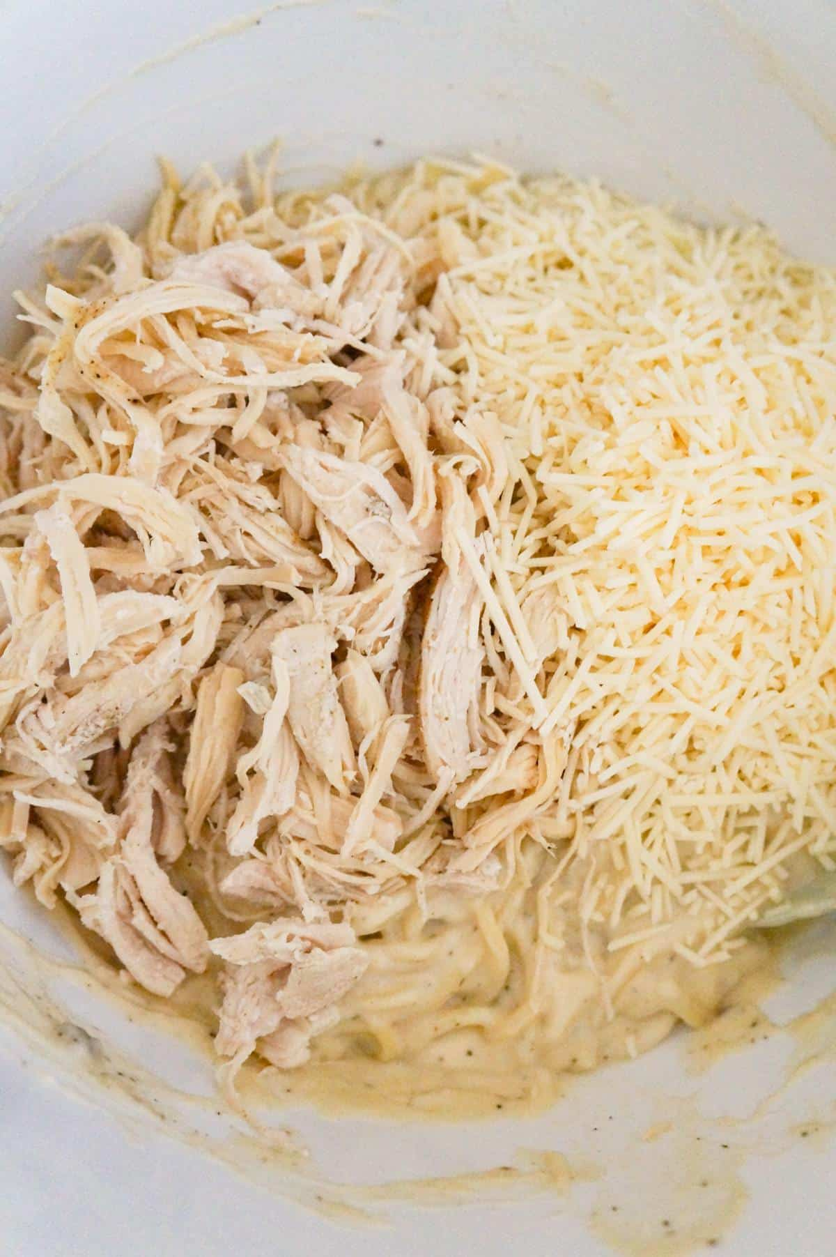 shredded chicken and shredded Parmesan on top of spaghetti in a mixing bowl