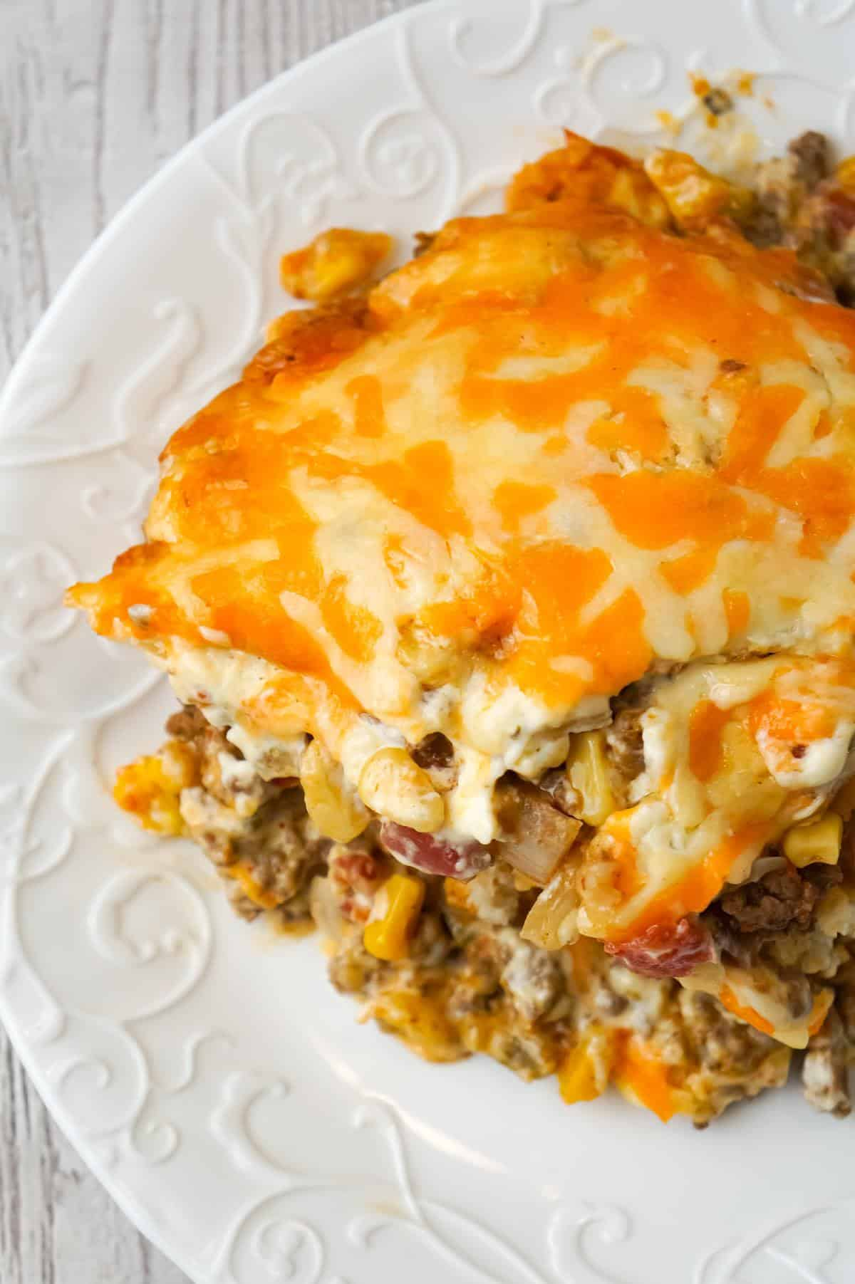 John Wayne Casserole is an easy ground beef casserole recipe with a biscuit base and loaded with diced tomatoes, corn, taco seasoning, cream cheese, mozzarella and cheddar.
