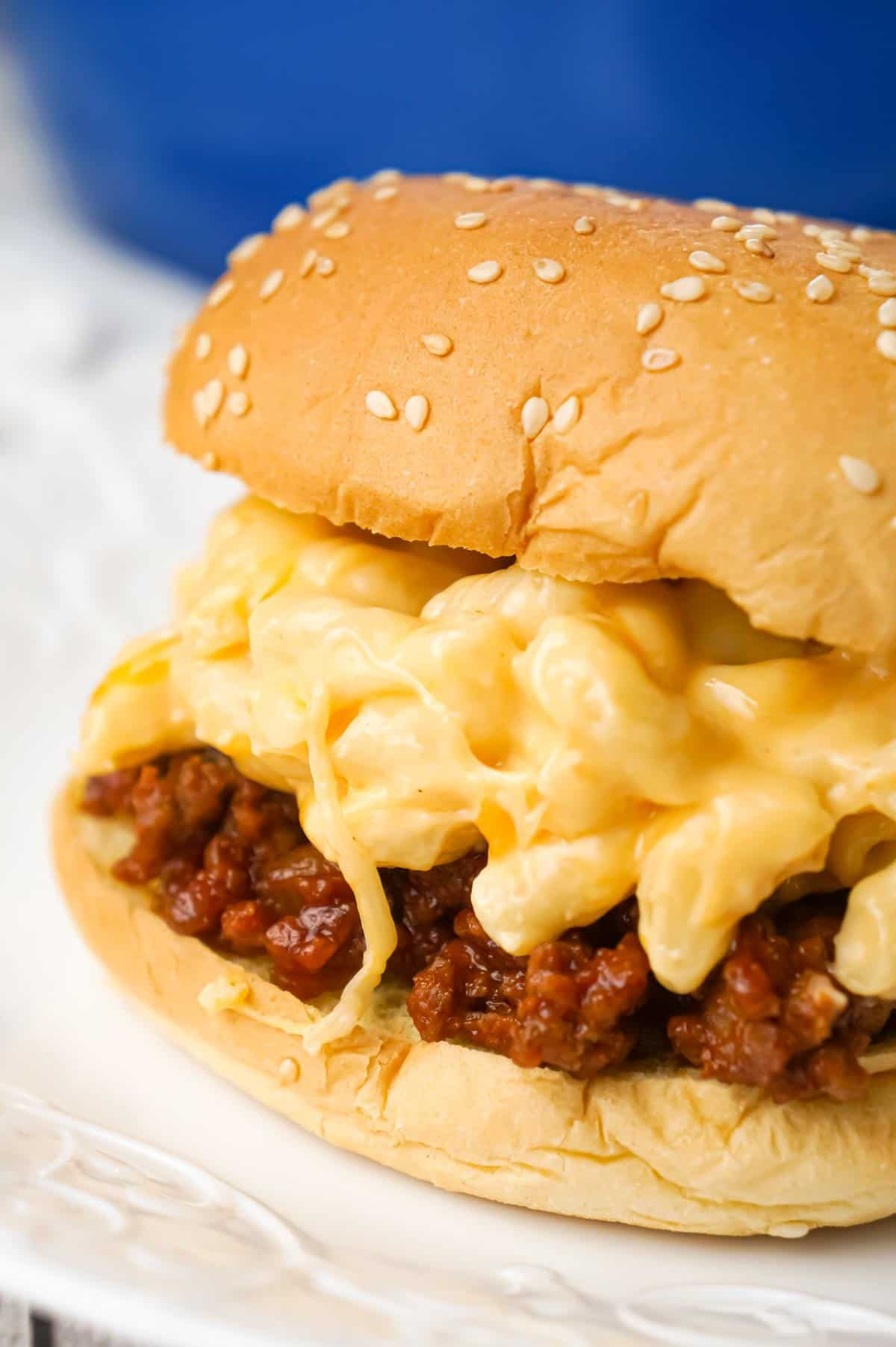 Mac and Cheese Sloppy Joes are hearty ground beef sandwiches topped with macaroni and cheese.
