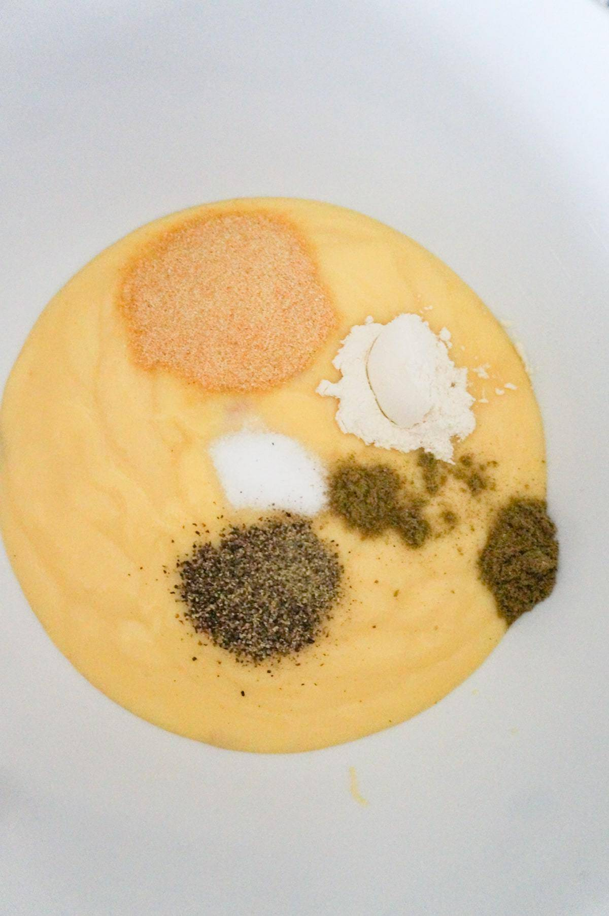 spices on top of condensed cream of chicken soup in a mixing bowl
