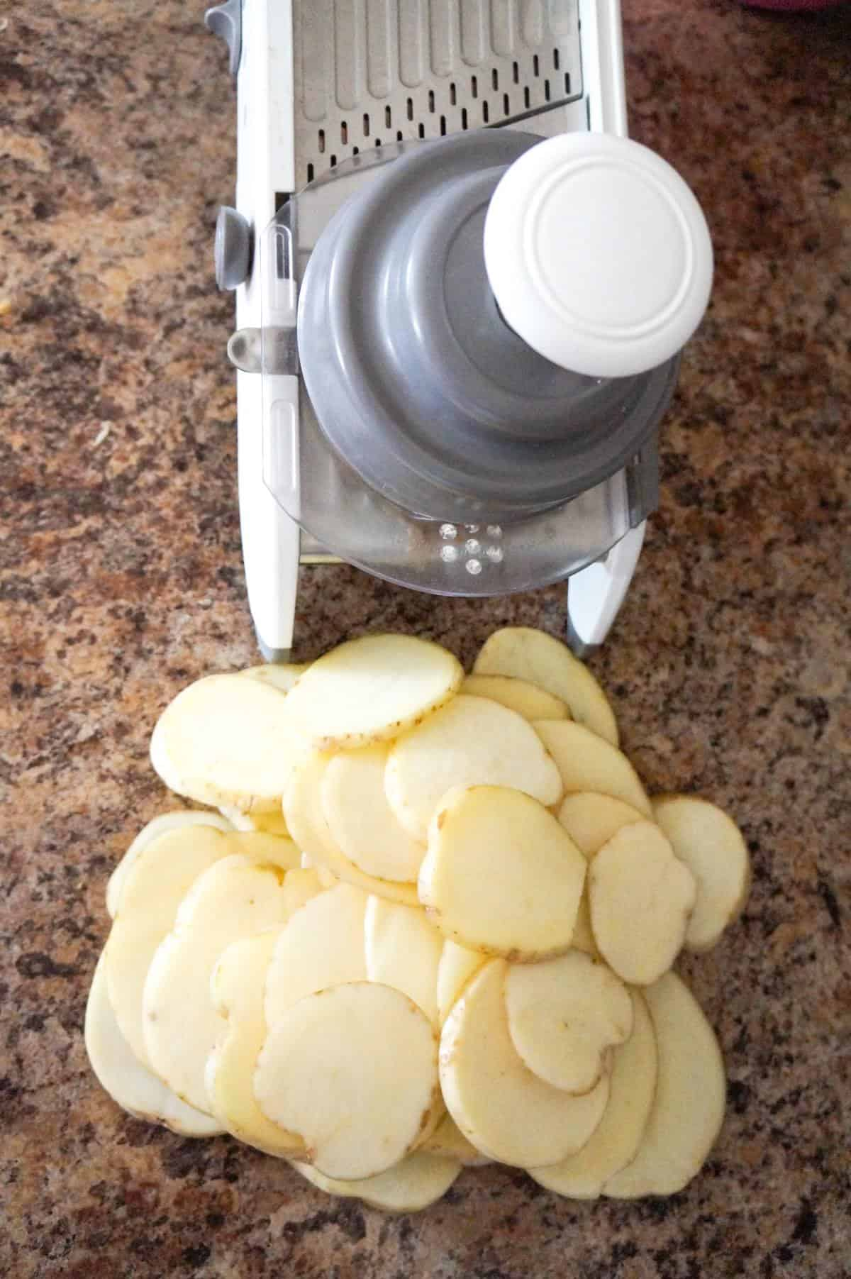sliced potatoes and a mandoline slicer
