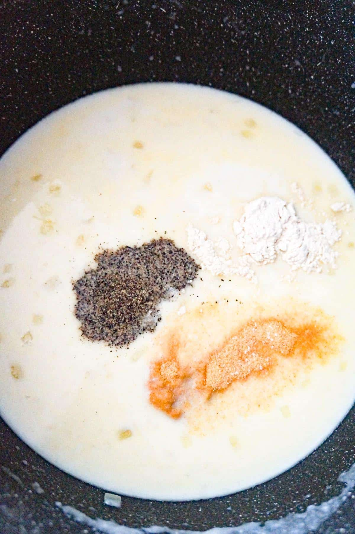 spices on top of creamy onion soup in a large pot